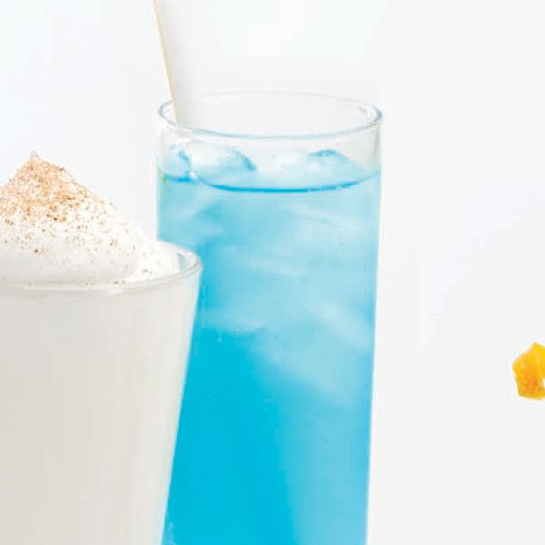 Tall slender glass filled with ice cubes, Blue-Hawaii drink and a white straw