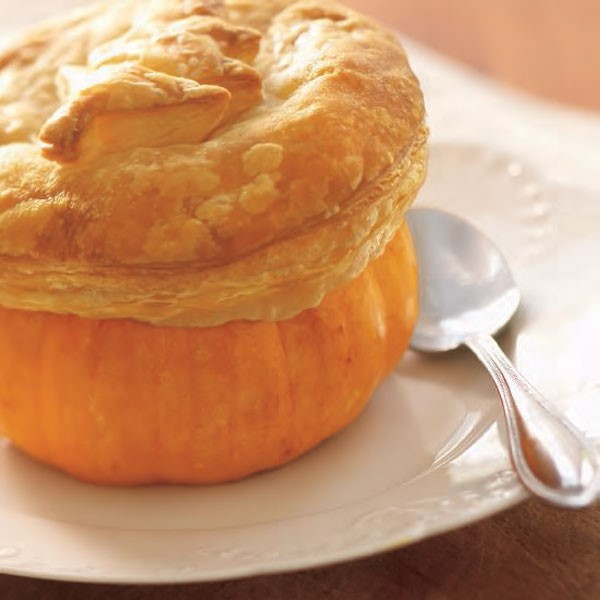 Pumpkin bowl topped with puff pastry on white plate with spoon