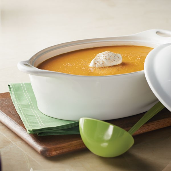Dish of creamy carrot and sweet potato soup topped with Greek yogurt and sprinkled nutmeg