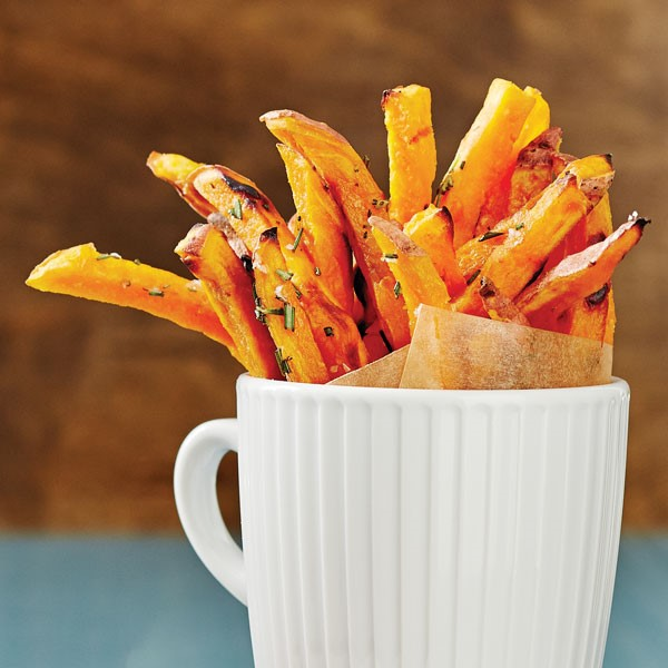 White mug filled with baked sweet potato fries garnished with fresh herbs