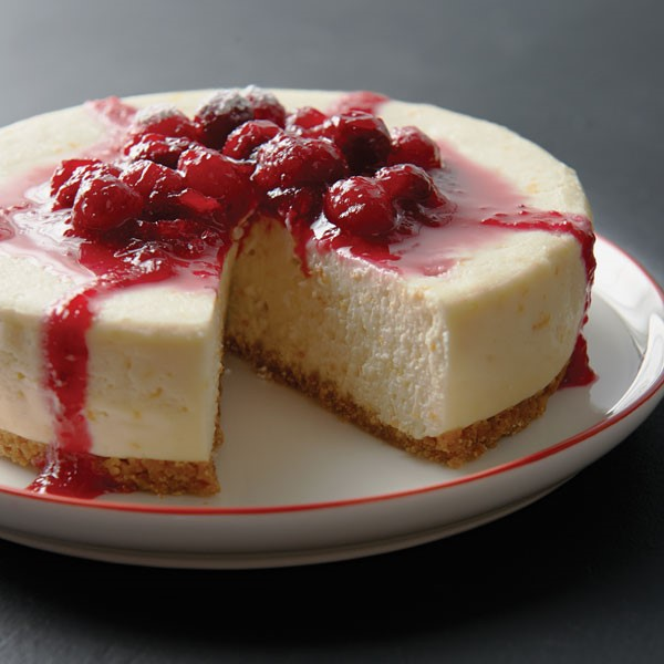 Plate of cheesecake layered with graham cracker crust, cheesecake filling and raspberries