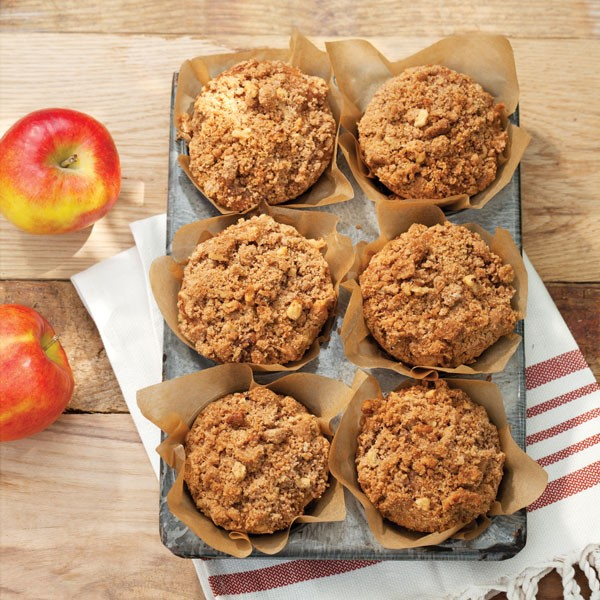 Apple muffins in tin with crumble on top surrounded by fresh apples