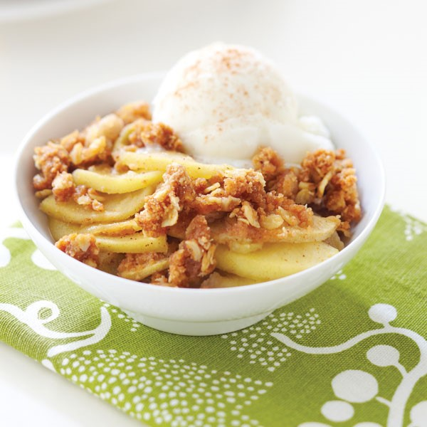 Bowl of apple crisp served with a scoop of vanilla ice cream topped with cinnamon