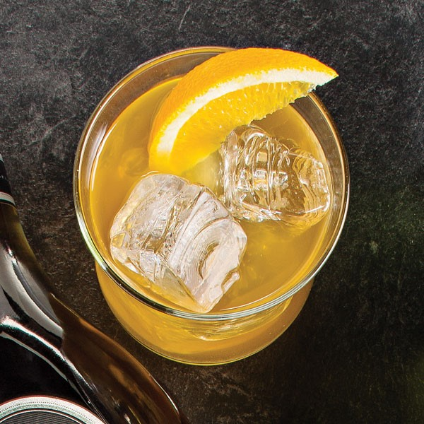 Cocktail glass filled with ice cubes, orange cocktail, and an orange wedge for garnish