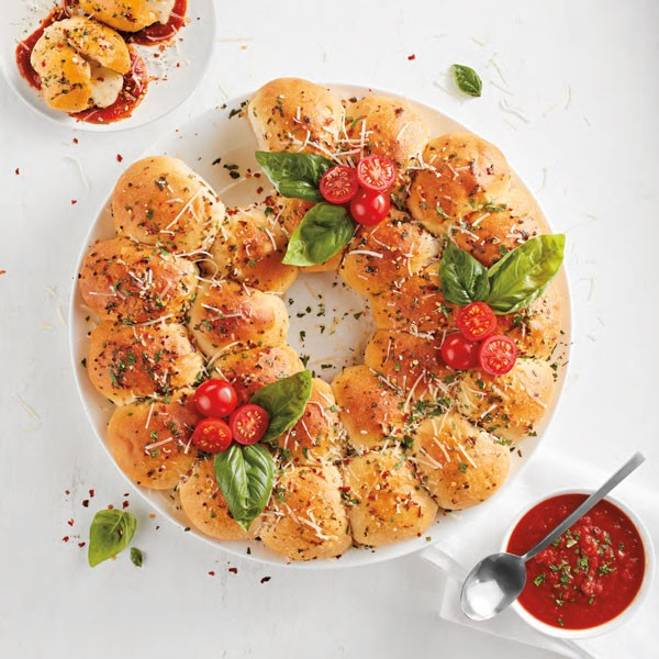 Platter of rolls topped with mozzarella, tomatoes, basil and served with tomato basil dipping sauce