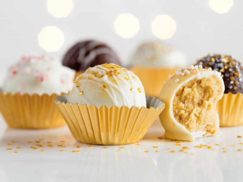 Gold-colored tins filled with white chocolate and milk chocolate cookie truffles