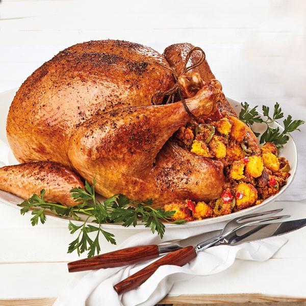 Platter of turkey filled with cornbread chorizo stuffing next to serving utensils