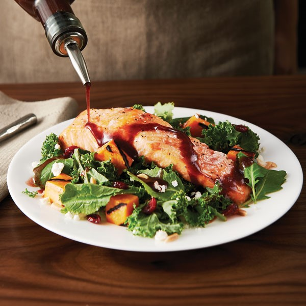 Plate of salad topped with salmon and sweet pototo wedges and drizzled with balsamic vinaigrette