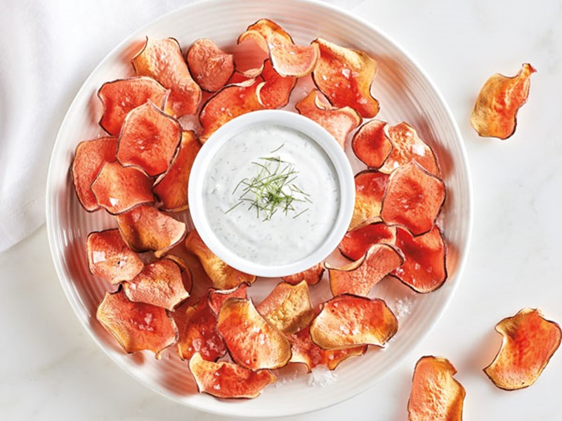 Plate of baked sweet potato chips surrounding a bowl of dill dip