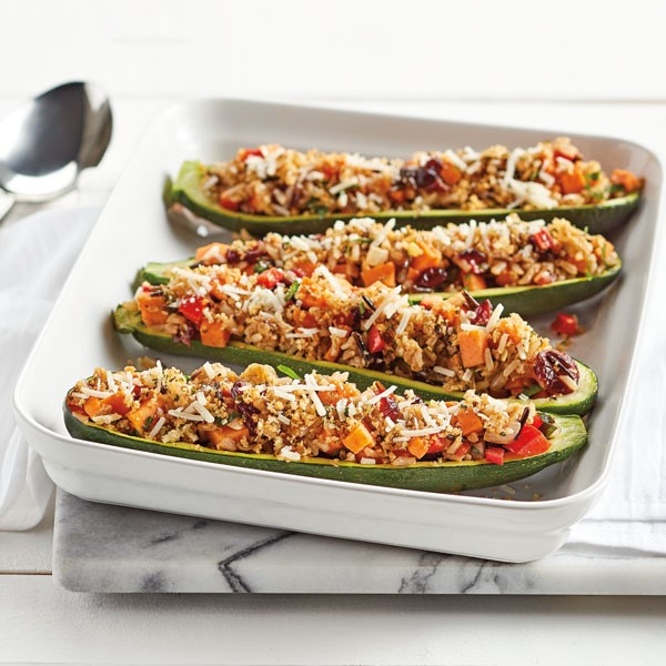 Tray of zucchini boats filled with sweet potato, red bell pepper, onion, cranberries, rice, breadcrumbs and parmesan cheese
