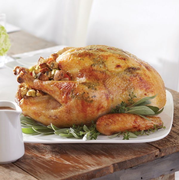 Whole roasted turkey with stuffing and garnished with fresh herbs
