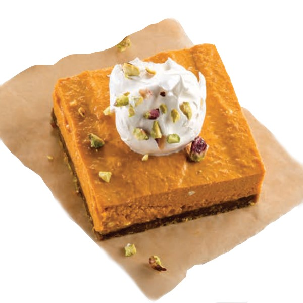 Pumpkin bar on parchment paper, topped with whipped topping and crushed pistachios