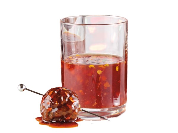 Skewered meatball coated in barbecue sauce next to cup of barbecue sauce