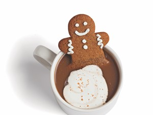 gingerbread man cookie in a mug full of coffee and milk