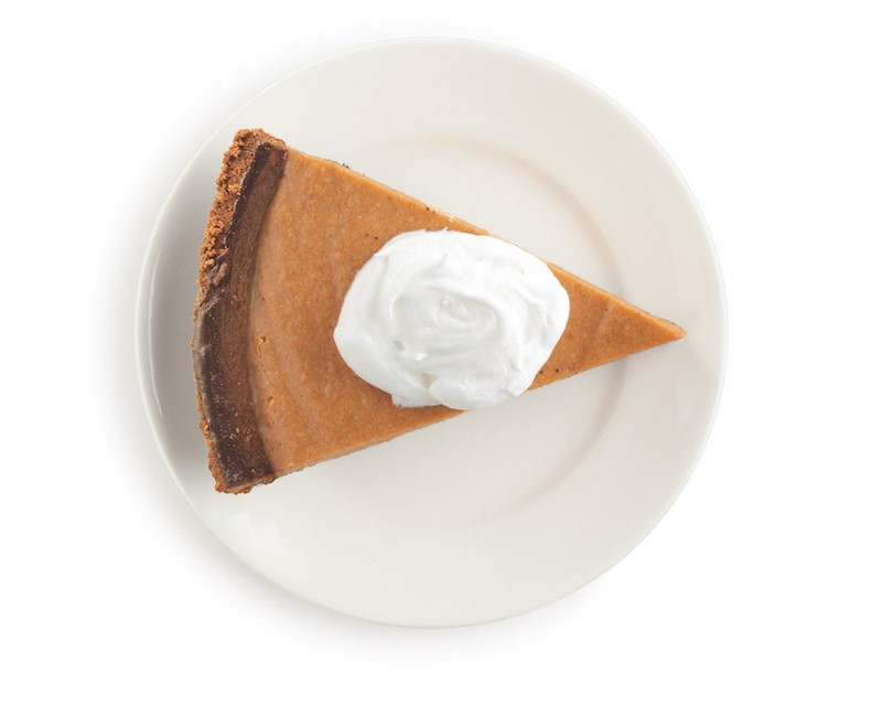 piece of pumpkin pie on a plate with whipped cream on top