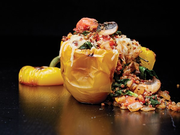 Yellow bell pepper filled with onion, tomato, quinoa, spinach and herbs