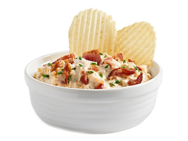 White bowl filled with dip and topped with cooked chopped  bacon, chopped chives, and two crinkled potato chips
