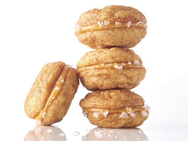 Snickerdoodle cookie sandwiches filled with caramel and dipped in coarse salt