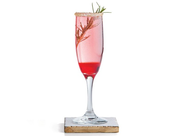Sugar-rimmed glass filled with grenadine and champagne and garnished with a rosemary sprig