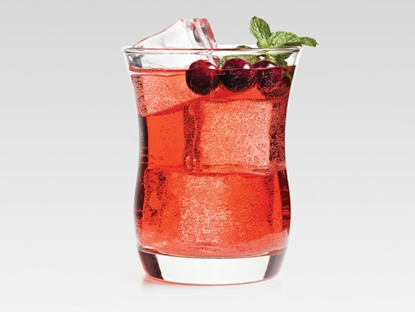 Glass of Crown cranberry cocktail, garnished with cranberries and mint sprigs