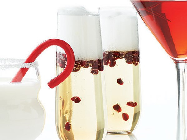 Two glasses of bubbly champagne cocktail, filled with pomegranate seeds