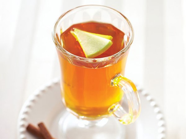 Glass of apple cider topped with apple slices and served with cinnamon sticks