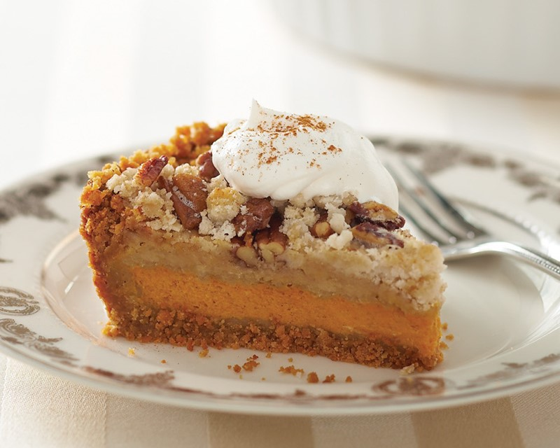 Slice of pumpkin pecan layer pie, topped with whipped topping and cinnamon on a plate