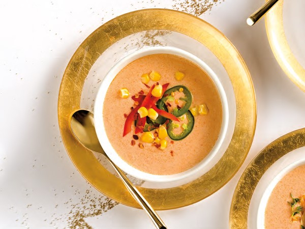 Bowl of lobster bisque garnished with red bell pepper, corn and jalapenos
