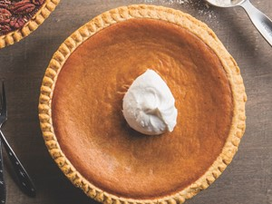 whole pumpkin pie with a dollop of whipped cream