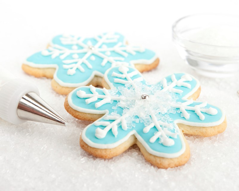 snowflake-shaped cookie with blue icing outlined in white