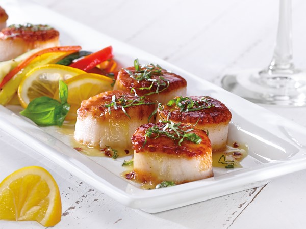 Platter of seared scallops, garnished with fresh herbs and served with vegetables and lemon slices